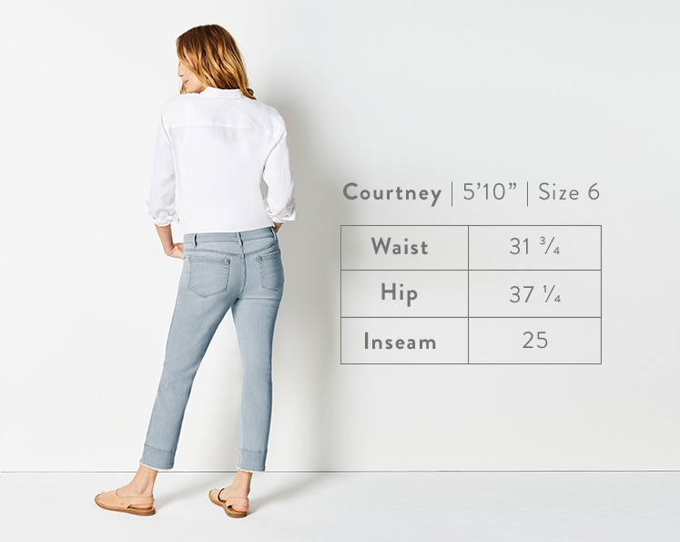 A rear-facing photo of Courtney modeling Authentic Fit Fringed-Hem Cropped Jeans. Courtney is 5 feet 10 inches tall, and a size 6. Waist: 31 3/4 inches, Hip: 37 1/4 inches, Inseam: 25 inches.