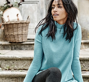 woman sitting on stair case wearing a sweater