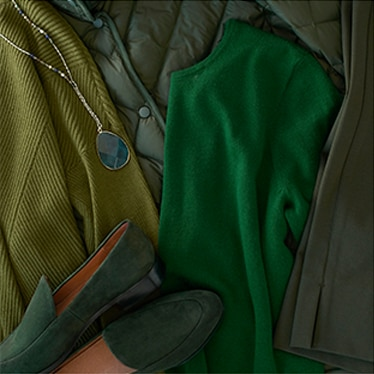 Different items of clothing in varying shades of green with a necklace