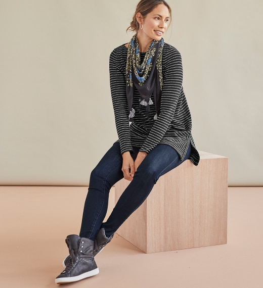women wearing sneakers, jeggingsm and a long stripe sleeve shirt. She is sitting down with leg criss crossed