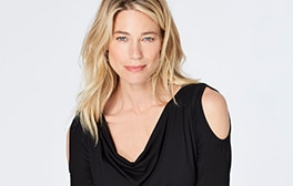 Woman wearing flowy black shirt with open shoulders