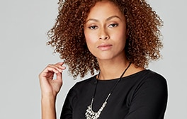 Woman wearing a black blouse and black/silver necklace
